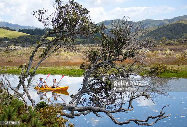 A tourist couple with their kayak rowing through landscape and coastline on November 27 2010 in Coromandel Coromandel Peninsula North Island New...
