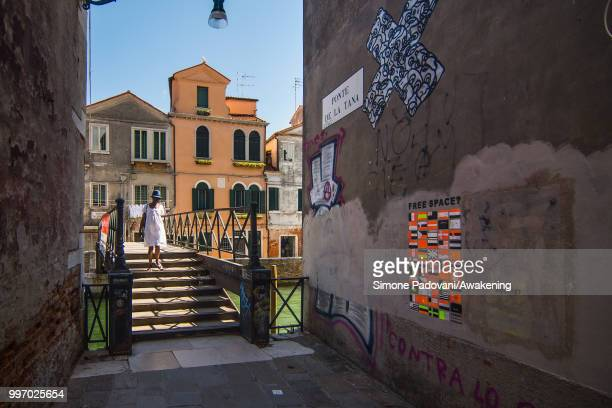 A tourist crosses De La Tana bridge close to Arsenale entrance of Biennale of Venice with the wall covered by graffiti and tags on the way to...