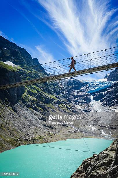 tourist crossing trift bridge, switzerland - 氷河湖 ストックフォトと画像
