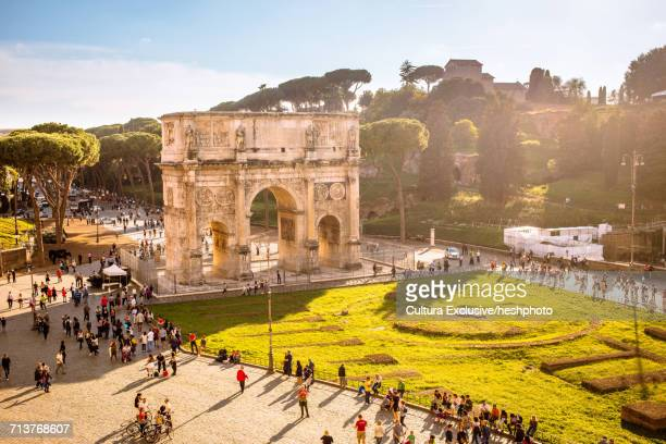 tourist crowd at the arch of constantine viewed from the colosseum, rome, italy - heshphoto stock pictures, royalty-free photos & images