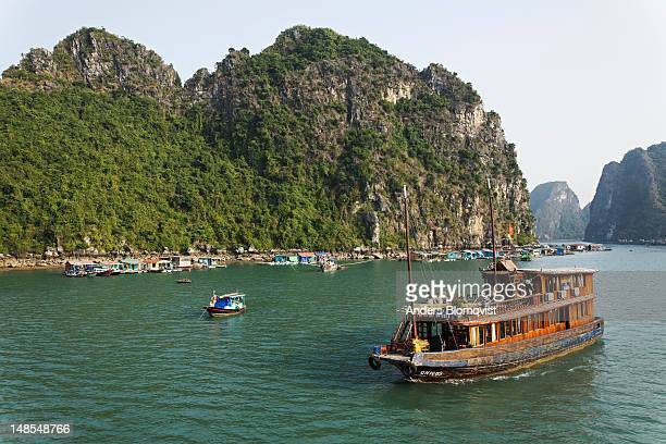 Tourist cruise boat passing typical floating village among limestone islands of Halong Bay.