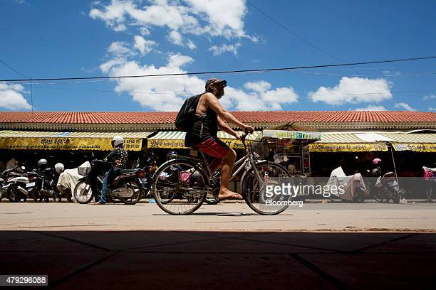 A tourist cycles past Psah Chah market also known as Old Market in Siem Reap Cambodia on Monday June 29 2015 Angkor in the northern province of Siem...