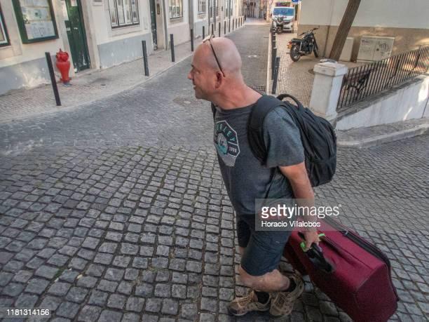 A tourist drags his luggage uphill in Calçada Salvador Correia de Sa Santa Catarina historical neighborhood on October 15 2019 in Lisbon Portugal...