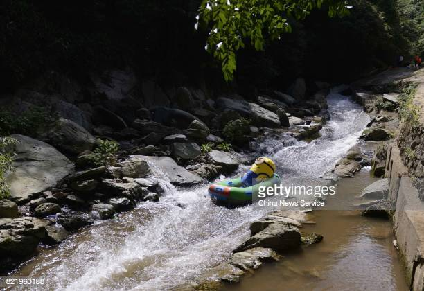 A tourist dressed as Minions drifts in a river at Lianyuan on July 24 2017 in Loudi Hunan Province of China Tourists in the Minions costumes enjoyed...