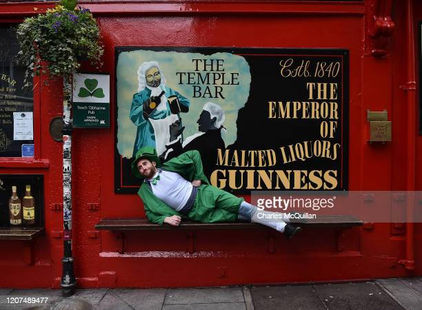 A tourist dressed in a leprechaun outfit sits outside the Temple Bar following the cancellation of the annual Saint Patricks Day parade and...