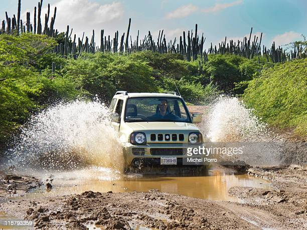 Tourist drives his Suzuki four-wheel drive through the mud in the hills of Bonaire on January 28, 2011 on the island of Bonaire. Bonaire has earned a...