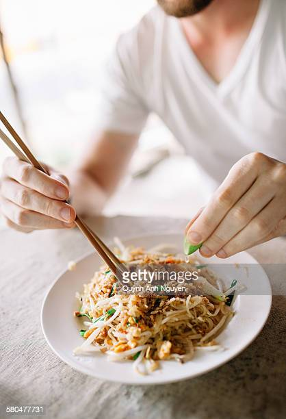 A tourist eating Pad Thai, famous rice noodle dish