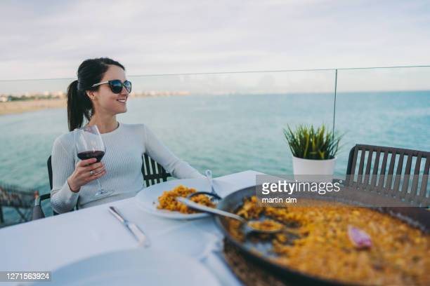 tourist eating paella in valencia - valencia spain stock pictures, royalty-free photos & images