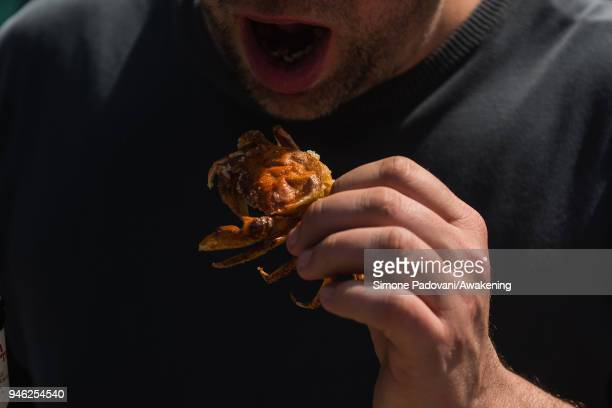 A tourist eats a 'Moeca' after a tour of the fishing in Burano on April 14 2018 in Venice Italy At the beginning of the Spring the crabs go through a...