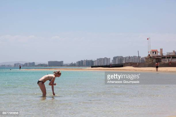 Tourist enjoy the beach infront of 'Forbidden Zone' of Varosha district on July 06, 2010 in Famagusta, Cyprus. Abandoned and decaying Buildings of...