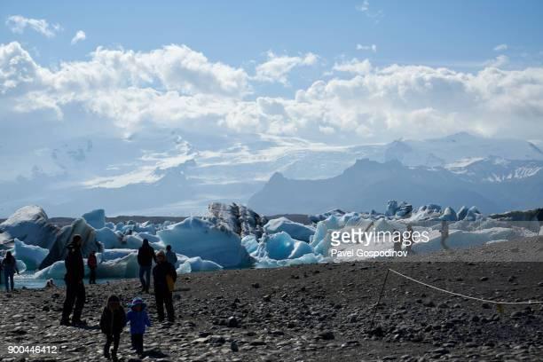 Tourist enjoying the magnificent Jökulsárlón Glacier Lagoon in Iceland
