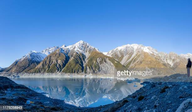 tourist enjoying the view of a mountain range reflected in a glacial lake - snowcapped mountain stock pictures, royalty-free photos & images