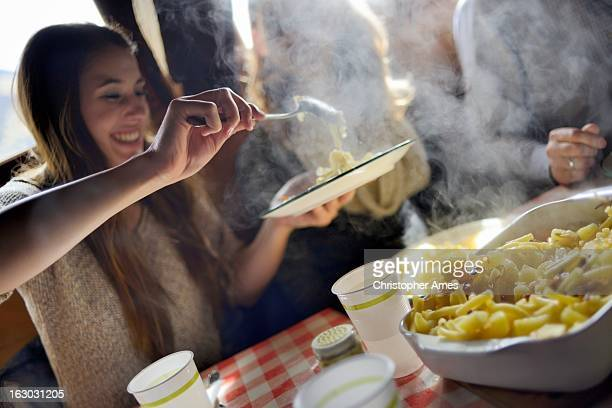 Tourist enjoying traditional Swiss meal Alplermagronen