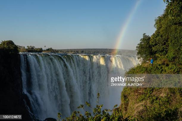 A tourist enjoys a view the waterfalls from the 'Devil's Cataract' where water rumbles down at height of seventy three metres on June 29 2018 at...