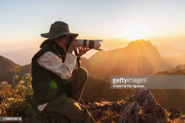 tourist enjoys sunset with camera at doi luang chiang dao in chiang mai, thailand. - photographer stock pictures, royalty-free photos & images