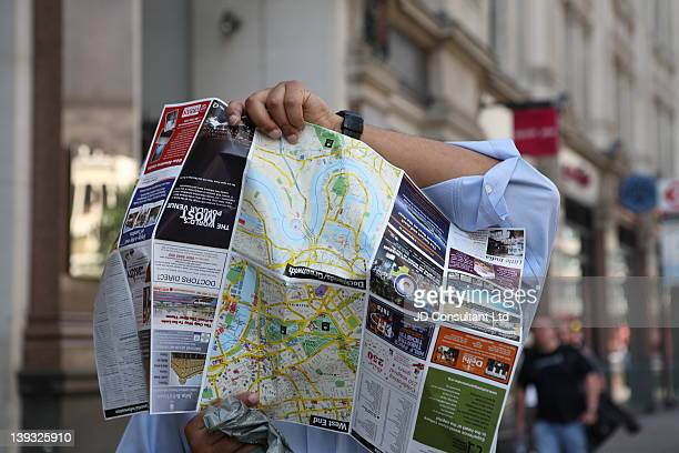 Tourist entangled in a London tourist map, on Regent street, London.