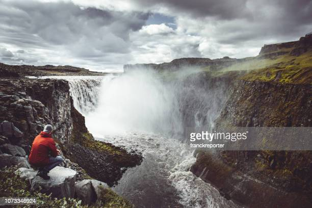 tourist explorer at gulfoss waterfall in iceland - gullfoss falls stock photos and pictures