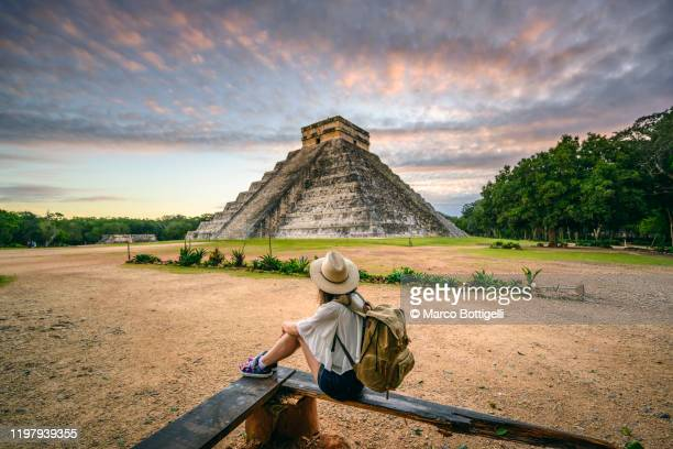tourist exploring chichen-itza archaeological site, yucatan, mexico - mexiko stock-fotos und bilder