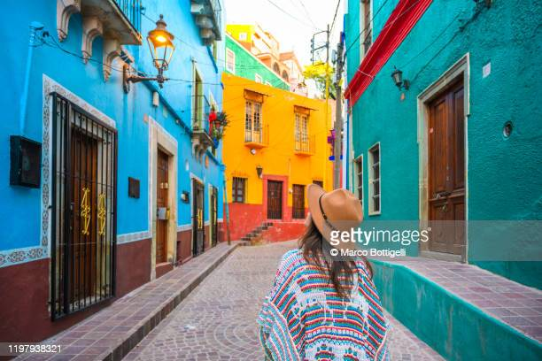 tourist exploring colorful backstreets in guanajuato, mexico - guanajuato stock pictures, royalty-free photos & images