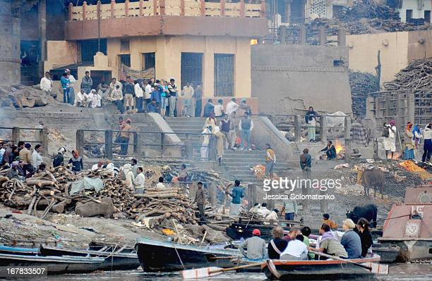 CONTENT] Tourist family and holy men watch as bodies are burned at a burning ghat at the edge of the Ganges in Varanasi India
