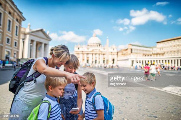 Tourist family checking directions near St. Peter's Square, Rome, Italy