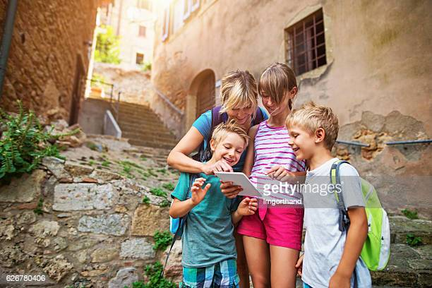 Tourist family checking map on tablet in an Italian town