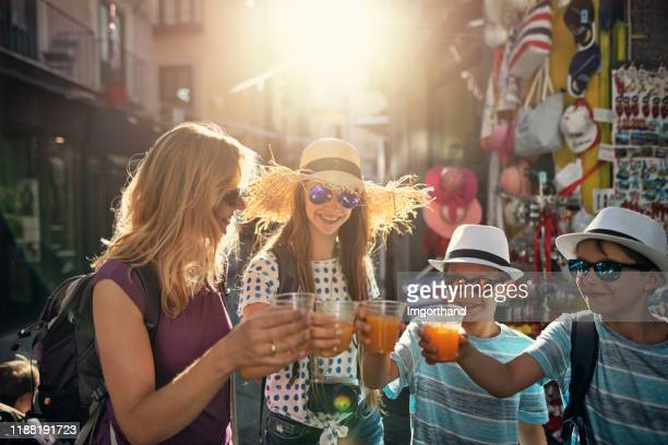tourist family drinking fresh orange juice in italian town - imgorthand stock photos and pictures