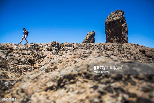 A tourist family member of the photographer walks past Roque Nublo a volcanic rock on July 26 2015 near Tejeda in Gran Canaria Spain Gran Canaria...