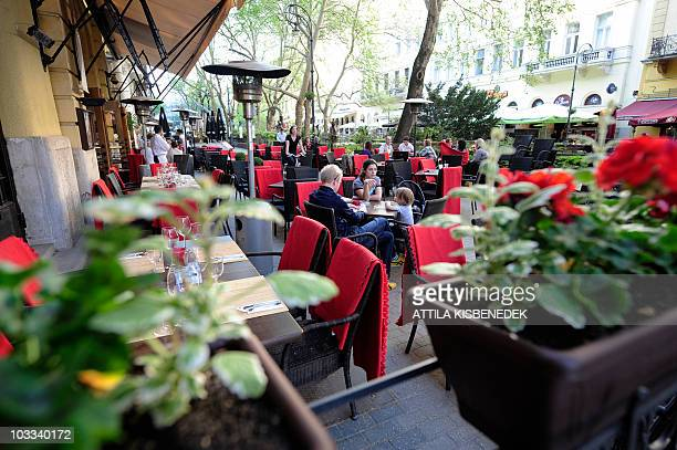 A tourist family sits around the table in an openair restaurant of Budapest at the Ferenc Liszt square on April 30 2010 AFP PHOTO / ATTILA KISBENEDEK