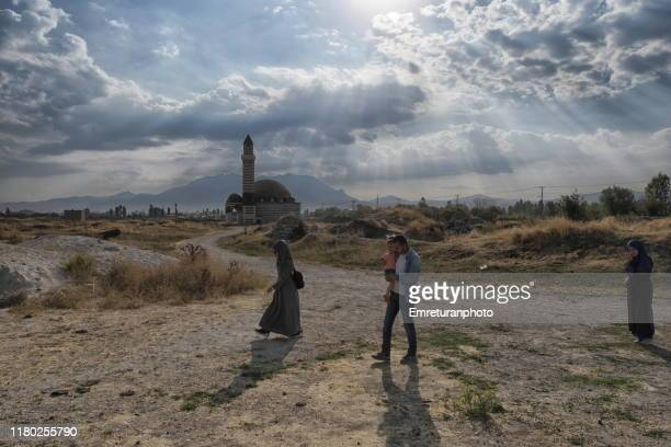 tourist family visiting old van city ruins with kaya celebi mosque at the background - emreturanphoto stock pictures, royalty-free photos & images