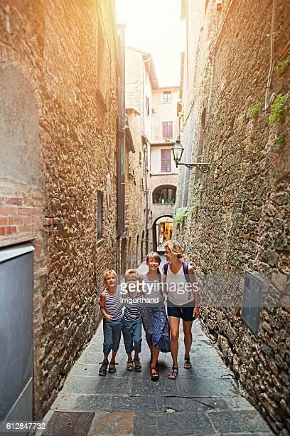 Tourist family walking narrow street in Italian town Volterra Tuscany