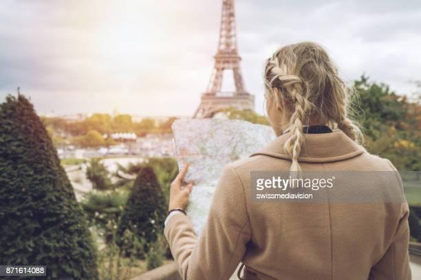 femelle de la touriste, à paris à la tour eiffel, détenant une carte - carte france photos et images de collection