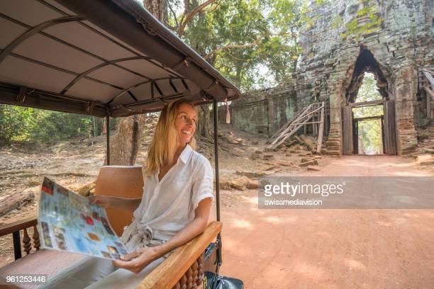 Tourisme femme regardant sites carte sur pousse-pousse lors d'une visite de l'ancien temple de Angkor Wat, au Cambodge, l'Asie du sud-est. Les gens voyagent partage concept de communication