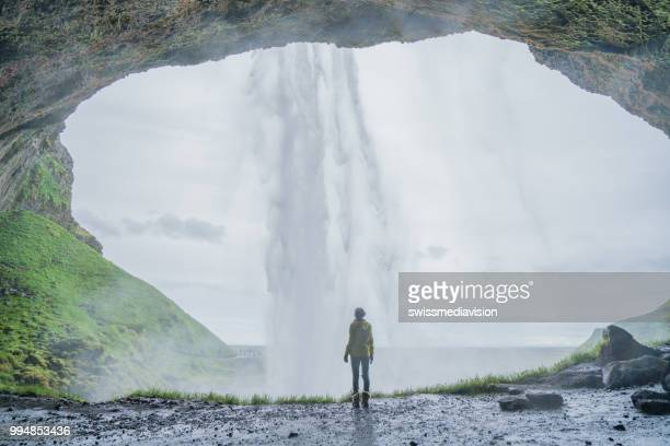 Tourist female traveling in Iceland stands behind magnificent waterfall and contemplates the nature, people travel adventure concept