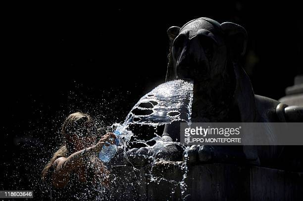 A tourist fills up her plastic bottle with water from a fountain of central Rome's Piazza del Popolo on July 9 2011 Italians were being urged to stay...