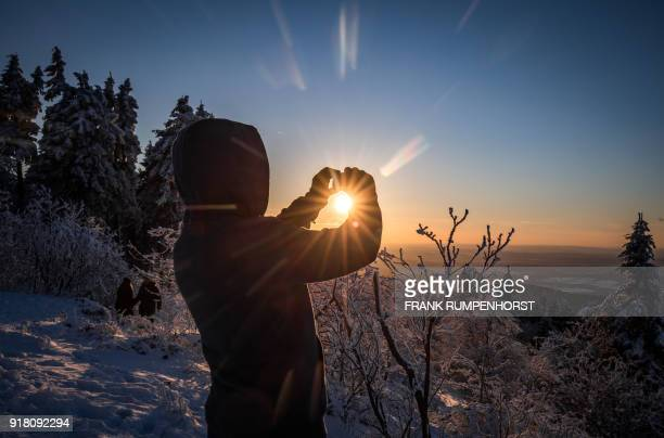 A tourist films the sun setting on the winter landscape at the Grosser Feldberg mountain in the Taunus region near Schmitten western Germany on...