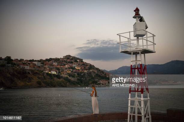 A tourist fishes at the port of Mithymna on the northeastern island of Lesbos on August 3 2018