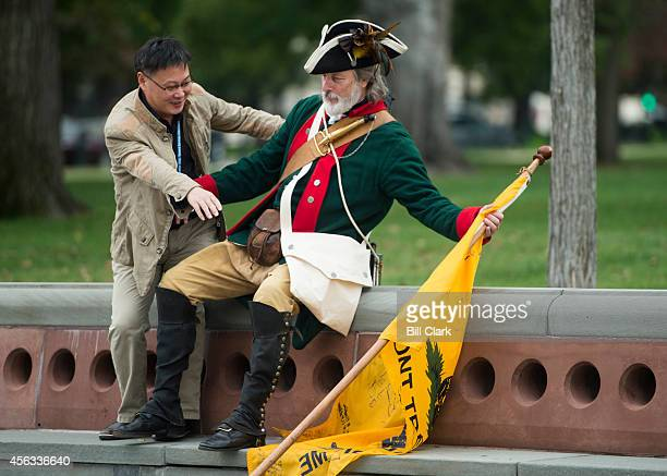 A tourist from China reaches for William Temple's Gadsden flag as he sits down to pose for a photo with the tea party activist on the East Plaza of...