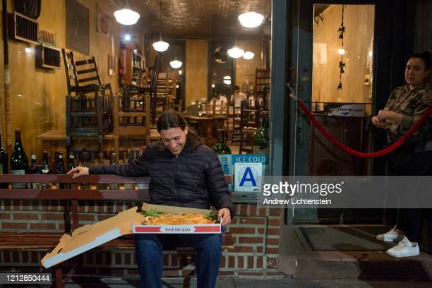 A tourist from England is overjoyed to try a pizza from the popular Lucali's restaurant on March 16 2020 in the Carroll Gardens neighborhood of...