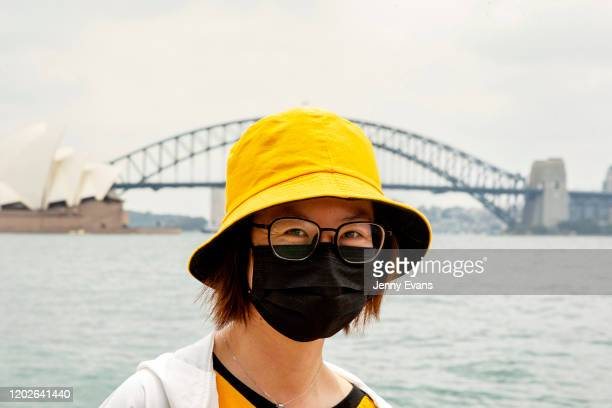 Tourist from Hong Kong is seen wearing a mask at Mrs Macquarie's Chair on January 29, 2020 in Sydney, Australia. The coronavirus, which originated in...