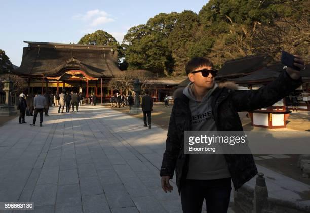 A tourist from South Korea poses for a selfie photograph at the Dazaifu Tenmangu shrine in Dazaifu Fukuoka Japan on Friday Dec 22 2017 Fukuoka on...