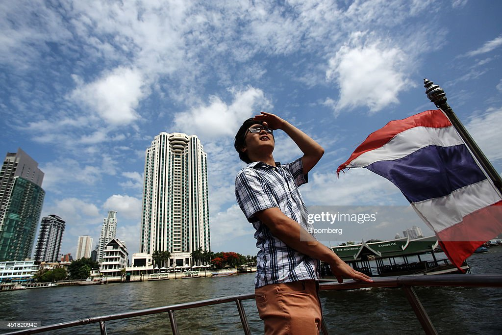 A tourist from South Korea stands on the deck of a tourist boat on the Chao Phraya river as it navigates past the Peninsula Hotel, center, in Bangkok, Thailand, on Saturday, June 28, 2014. Through a dozen coups, a tsunami, financial upheaval, floods and riots, Bangkok keeps bouncing back. With each crisis, tourism numbers slump, stocks crash and investment dips, only to return stronger than before. Photographer: Dario Pignatelli/Bloomberg via Getty Images