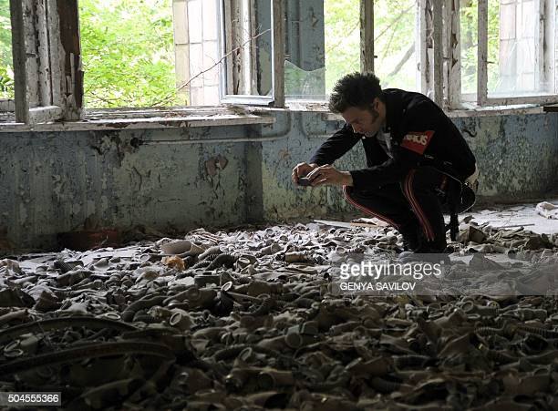 A tourist from Sweden takes picture of gas masks on the floor in a school in the abandoned and deserted town of Pripyat on September 16 2010...