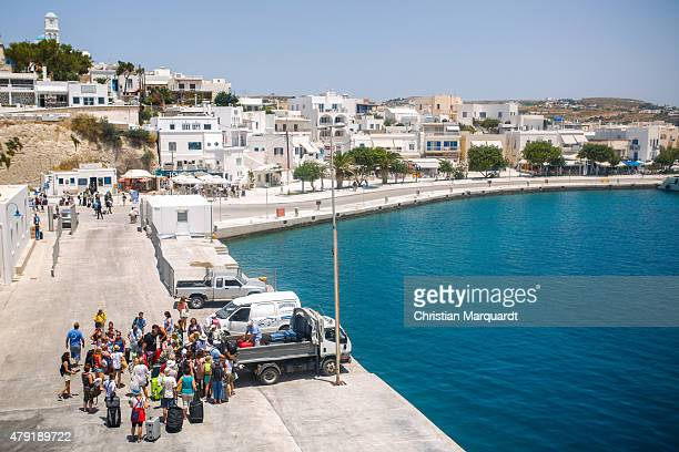 Tourist gather in a group at a port after leaving a ferry on the way to Sifnos island on June 16 2015 in Sifnos Greece Sifnos is a island in the...