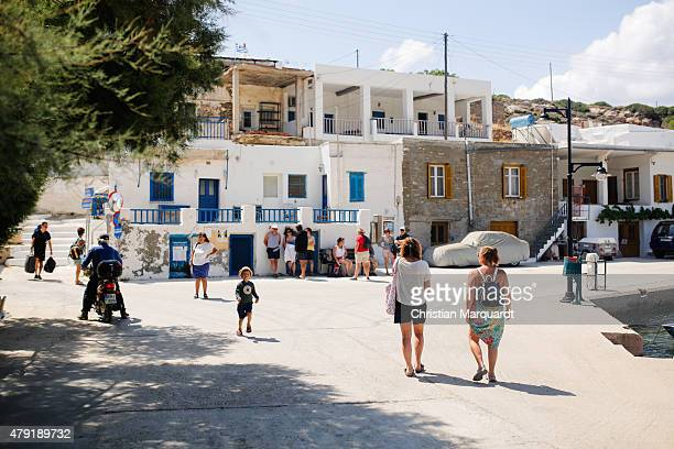 Tourist gather next to a bus station at the port during midday in the town of Faro on June 19 2015 in Sifnos Greece Sifnos is a island in the western...