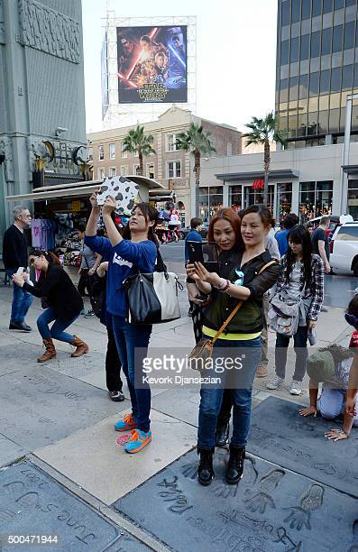 Tourist get their pictures taken on top of hand and foot print of Hollywood movie stars at TCL Chinese Theatre where a ear Star Wars fans camp out...