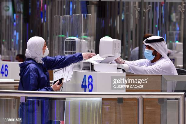 Tourist gets her papers checked upon arrival at Teminal 3 at Dubai airport, in the United Arab Emirates, on July 8 as the Gulf emirate reopens to...