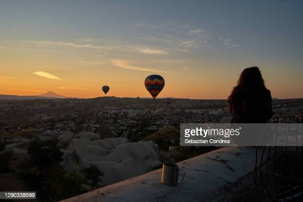 tourist girl meet sunrise in cappadocia with air balloon in sky, cappadocia, turkey. volcanic mountains in goreme national park. - royal tour stock pictures, royalty-free photos & images