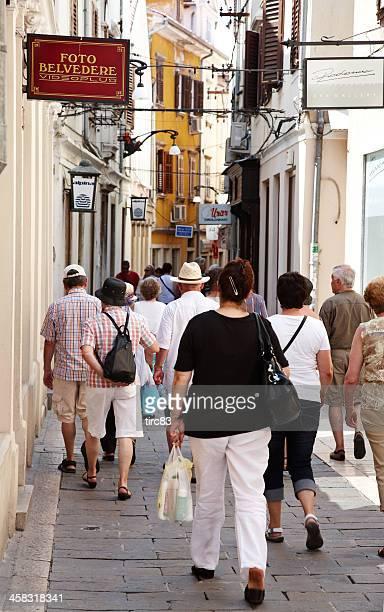 tourist group walking through narrow slovenia streets - koper stock photos and pictures
