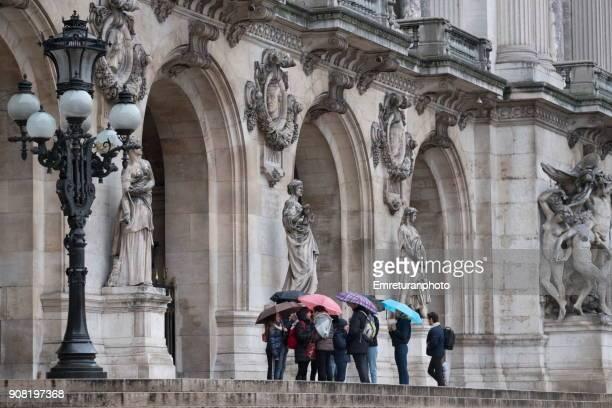 Tourist group with umbrellas in front of Opera Garnier building in Paris.